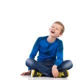 Roześmiany młody chłopiec obsiadanie na podłoga. fotografia royalty free