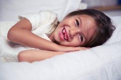 Roześmiany małej dziewczynki lying on the beach w łóżku Obrazy Stock
