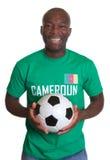 Roześmiany piłki nożnej fan od Cameroon z piłką fotografia stock