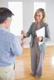 Roześmiany pośrednik handlu nieruchomościami trzyma teczkę i daje kluczowi nabywca Obraz Stock