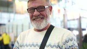 Roześmiany starsza osoba mężczyzna z szkłami i szara broda przy lotniskiem Zamknięty portret, czekać na lot zbiory wideo