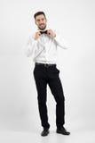 Roześmiany szczęśliwy młody brodaty elegancki mężczyzna przystosowywa łęku krawat patrzeje kamerę Zdjęcie Royalty Free