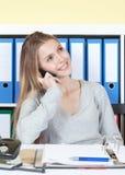 Roześmiany uczeń przy telefonem przy biurem obrazy stock