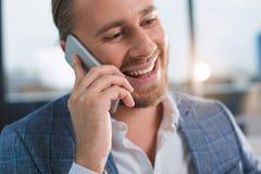 Roześmiany urzędnik komunikuje na telefonie komórkowym Zdjęcia Royalty Free
