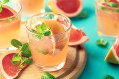 Roze alcoholische cocktail met grapefruit, ijs en min stock foto's