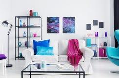 Roze algemene en blauwe kussens op witte bank in zolderbinnenland met lijst, lamp en affiches Echte foto stock afbeelding