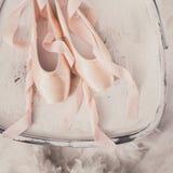 Roze ballet pointe schoenen en veer op witte houten achtergrond Royalty-vrije Stock Afbeeldingen