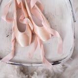 Roze ballet pointe schoenen en veer op witte houten achtergrond Royalty-vrije Stock Foto's