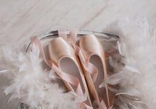 Roze ballet pointe schoenen en veer op witte houten achtergrond Royalty-vrije Stock Afbeelding