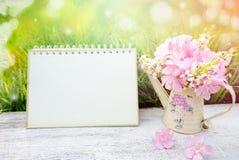 Roze bloem, blanco paginadocument van kalender over aard groen gras in zachte pastelkleurtoon Royalty-vrije Stock Fotografie