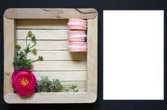 Roze bloem op een houten kader Houten kader op een zwarte achtergrond Makarons op een houten achtergrond royalty-vrije stock afbeelding