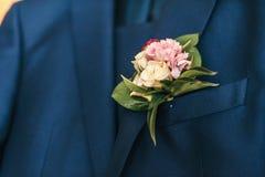 Roze bloemen in het knoopsgat van de bruidegom stock fotografie