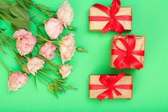 Roze bloemen met bladeren en drie giftdozen op groene achtergrond royalty-vrije stock afbeeldingen