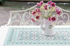 Roze bloemen, papaver in uitstekende theepot op terraslijst stock fotografie