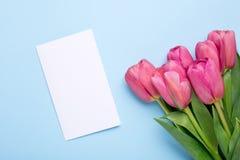 Roze bloementulpen en huidige kaart op een blauwe achtergrond stock foto