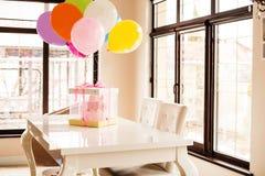 roze cake bij de viering van de eerste verjaardag van het meisje, de ballons en de gelukwensen, 1 jaar stock fotografie