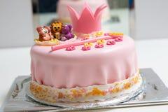 Roze cake van een kleine prinses met een kroon en dierlijke cijfers Verjaardag één éénjarige Het concept van de vakantie royalty-vrije stock foto