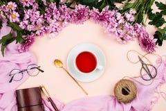 Roze chrysantenbloemen, madeliefjes, hibiscusthee, roze sjaal, glazen en notitieboekje Royalty-vrije Stock Foto's