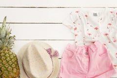 Roze denimborrels en een t-shirt, strohoed, ananas Witte oude houten achtergrond Royalty-vrije Stock Afbeeldingen