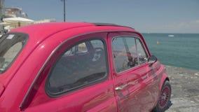 Roze die retro auto op pijler in toevluchtstad, reis en vakantie, de zomertijd wordt geparkeerd stock videobeelden