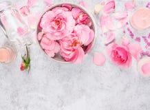Roze die rozenschoonheidsmiddelen met room, fles, kaarsen, bloemblaadjes en overzees zout worden geplaatst Royalty-vrije Stock Fotografie