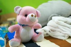 Roze die teddybeer op het bed wordt geplaatst stock fotografie