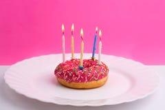 Roze doughnut op witte plaat zoals verjaardagscake met kaarsen op witte en roze achtergrond royalty-vrije stock foto's