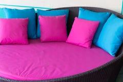 Roze en blauw hoofdkussen op bruine rotanbank Stock Foto