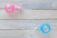 Roze en Blauwe fopspenen en zuigflessen op wit hout Royalty-vrije Stock Foto's
