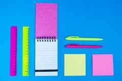 Roze en gele neonkantoorbehoeften op blauw bureau stock fotografie