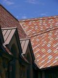 Roze en rode tegeldakspanen op een dak Stock Afbeelding