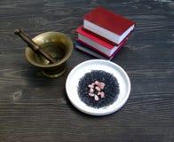 Roze en zwart zout, mortier, stamper en miniboeken stock fotografie