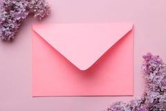 Roze envelop en tak van sering op een heldere in roze achtergrond Hoogste mening stock afbeelding