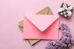 Roze envelop, lilac tak en giftdoos op een heldere in roze achtergrond Hoogste mening royalty-vrije stock foto's