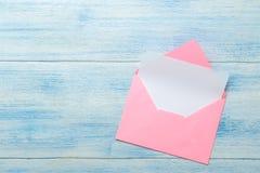 Roze envelop met lege vorm voor tekst op een blauwe houten lijst Hoogste mening stock foto's