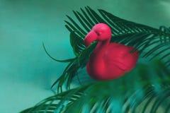 Roze flamingostuk speelgoed tussen palmbladeren Minimaal de zomerconcept stock afbeeldingen