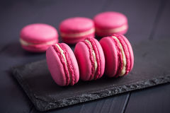 Roze frambozenmakarons op zwarte achtergrond Royalty-vrije Stock Foto's