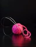 Roze garenballen op zwarte stock afbeeldingen