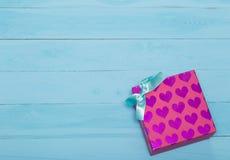 Roze giftdoos met harten en boog op blauwe achtergrond Stock Foto's
