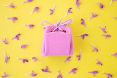 Roze giftdoos op een gele achtergrond met bloemen Feestelijk concept Vlak leg, hoogste mening stock afbeelding