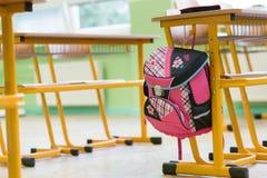 Roze girly schooltas en potloodgeval op een bureau in een leeg klaslokaal Eerste Dag van School royalty-vrije stock afbeelding
