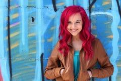 Roze haarmeisje tegen een blauwe muur royalty-vrije stock afbeeldingen