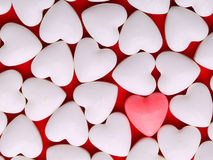 Roze hart tussen een stapel van witte harten De harten van het suikergoed Stock Afbeeldingen
