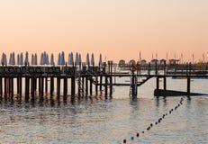 Roze hemel bij dageraad over het overzees De donkere silhouetten van de pijlers Stock Fotografie