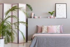 Roze hoofdkussens op grijs bed in het binnenland van de pastelkleurslaapkamer met palm en affiche op bedhead Echte foto stock afbeeldingen