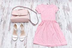 Roze kleding, witte schoenen en een beige zak modieus concept Stock Foto