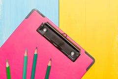 Roze klembord hoogste mening over kleurrijke achtergronden met exemplaarruimte voor tekst Stock Foto