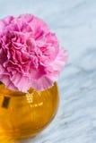 Roze kunstbloem in bruine ronde fles Stock Foto