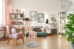 Roze leunstoel in comfortabele slaapkamer stock foto