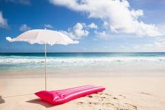 Roze luchtmatras en wit zonnescherm stock foto